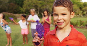 Portrait of smiling boy holding a water gun. On a sunny day 4k stock footage