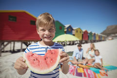 Portrait of smiling boy holding watermelon with family in background Stock Photo