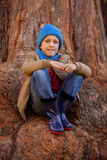 Portrait of smiling boy hugging knees while sitting on tree trunk. At park Stock Photo