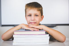 Portrait of smiling boy leaning on stack of books in class room. At school Stock Photography
