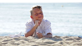 Portrait of smiling boy lying on beach. Portrait of smiling boy in elementary school age lying on beach on sunny weather stock footage