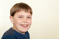 Portrait of smiling boy with missing tooth. A nine year old boy looks at the camera with a big, toothy smile.  He has light brown hair and brown eyes and is a Royalty Free Stock Photography