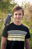 Portrait smiling boy with a parrot . Stock Images