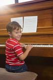 Portrait of smiling boy playing piano while sitting in classroom Royalty Free Stock Images
