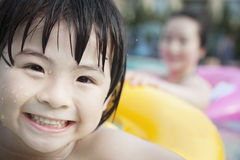 Portrait of smiling boy in the pool on a an inflatable tube with his mother in the background Stock Photo