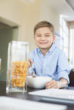 Portrait of smiling boy pouring corn flakes in bowl at home Stock Image