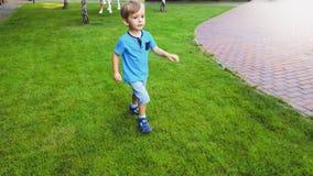 Portrait of smiling little boy running on grass lawn at park. Portrait of smiling boy running on grass lawn at park stock photo