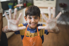 Portrait of smiling boy showing messy palms in kitchen Stock Image
