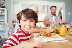 Portrait of smiling boy sitting at dining table Stock Photo