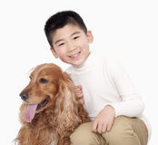 Portrait of smiling Boy sitting next to his dog, studio shot Royalty Free Stock Photos
