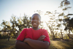 Portrait of smiling boy standing with arms crossed during obstacle course Royalty Free Stock Photography