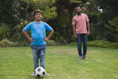 Portrait of smiling boy standing by soccer ball with father at park. Portrait of smiling boy standing by soccer ball with father in background at park stock image