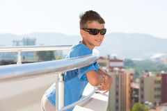 Portrait of a smiling boy stands on the balcony Stock Image