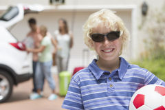 Portrait of smiling boy in sunglasses holding soccer ball in sunny driveway Royalty Free Stock Image