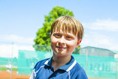 Portrait of a smiling boy at a tennis court Royalty Free Stock Photography