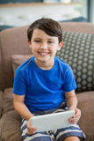 Portrait of smiling boy using digital tablet in living room Stock Photos