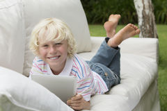 Portrait of smiling boy using digital tablet on outdoor sofa Royalty Free Stock Photo