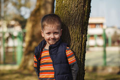 Portrait of the smiling boy which costs near a tree Royalty Free Stock Photo