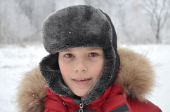 Smiling boy in winter clothes. Portrait of a smiling boy in winter clothes on a background of snow-covered forest Stock Photography