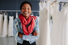 Portrait of smiling bridal store owner. Portrait of african female bridal store owner standing with her arms crossed and smiling. Woman tailor standing in Stock Photos