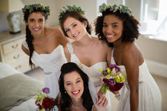 Portrait of smiling bride and bridesmaid in living room. At home stock photo