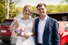 Portrait of smiling bride and groom posing at sunny day at park Stock Photos