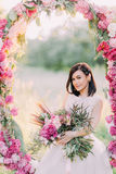 The portrait of the smiling bride holding the bouquet of flowers and sitting in the wedding peonies arch placed in the Stock Photography