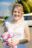 Portrait of smiling bride posing in park with wedding bouquet Stock Image