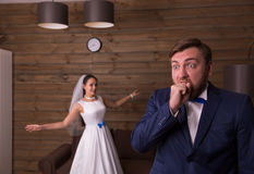 Portrait of smiling bride and surprised groom. Wooden background Stock Photos