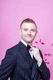 Portrait of smiling bridegroom in striped suit standing against pink background Royalty Free Stock Image