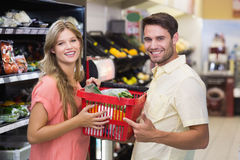 Portrait of smiling bright couple buying food products Royalty Free Stock Images