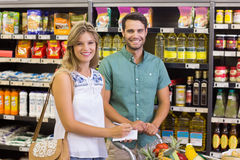 Portrait of smiling bright couple buying food products and uisng notebook Royalty Free Stock Photo