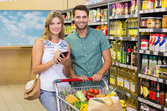 Portrait of smiling bright couple buying food products and using notebook Stock Images