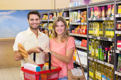 Portrait of smiling bright couple buying food products using shopping basket Royalty Free Stock Images