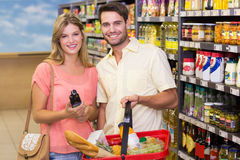 Portrait of smiling bright couple buying food products using shopping basket. At supermarket Royalty Free Stock Photo