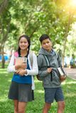 Cheerful school kids. Portrait of smiling brother and sister with backpacks and book standing outdoors Royalty Free Stock Image