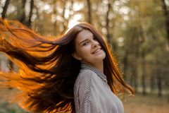 Portrait of a smiling brown-haired girl whose sunset sunlight shimmers in her hair. A young lady with a confident smile looks straight stock photos