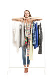 Portrait of smiling brunette behind hanger with clothes Royalty Free Stock Photo