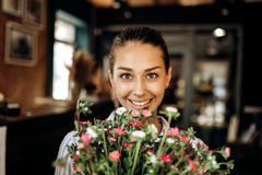 Portrait of smiling brunette girl with bouquet of pink and white stock photos