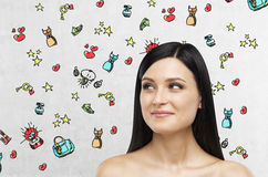A portrait of a smiling brunette lady who is looking at something on the right side. Colourful shopping icons are drawn on the con Royalty Free Stock Photo