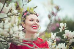 Portrait of a smiling brunette with a red lipstick lips in a red dress near a blooming magnolia stock images