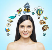 A portrait of smiling brunette who is surrounded by summer vacation icons which are drawn. A portrait of smiling brunette who is surrounded by summer vacation Royalty Free Stock Photography