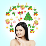 A portrait of a smiling brunette who is waiting for Christmas and New Year's Eve. Christmas-tree decorations are drawn on the ligh Stock Photos