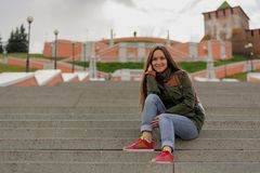 Portrait of smiling brunette woman on concrete steps in urban landscape, perspective effect, rule of thirds.  stock photo