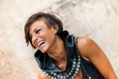 Portrait of a smiling brunette woman with light eyes and medieval-style leather clothing. In outdoors royalty free stock photo