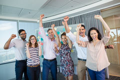 Portrait of smiling business colleagues cheering with fists up Stock Photo
