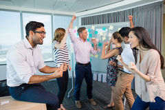 Portrait of smiling business colleagues cheering with fists up. In office Stock Photo
