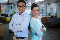 Portrait of smiling business colleagues standing back to back Stock Photos