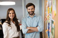 Portrait of smiling business colleagues standing by soft board Royalty Free Stock Photos