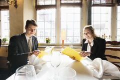 Portrait of smiling business couple with menus at restaurant table Royalty Free Stock Photo